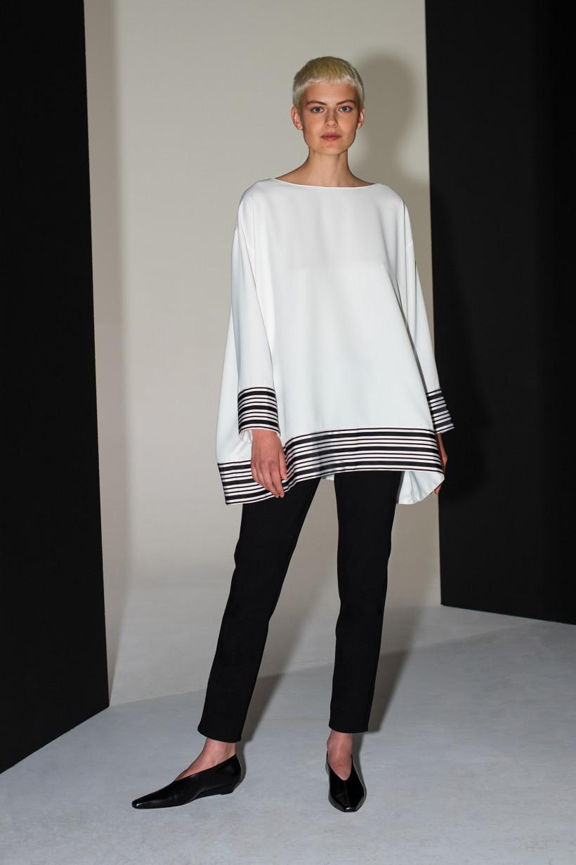 Rozkloszowana biała bluzka z ozdobną taśmą